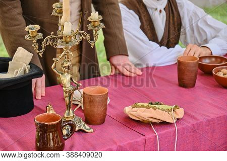 Old Table With Candelabra And People In Ancient Clothes. Top Hat And Old Dishes-cups And Mugs, Backg