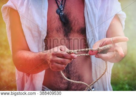 How To Tie Two Ropes Using A Sea Knot. A Young Man Demonstrates How To Tie Knots On A Rope. Backgrou