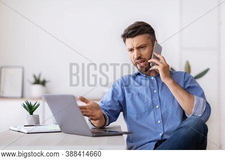 Angry Millennial Businessman Talking On Mobile Phone And Looking At Laptop Screen Working In Modern