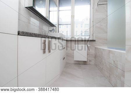 White Bathroom With A Window . Modern Apartment. Spacious Bathroom. White Shell. The Window In The B