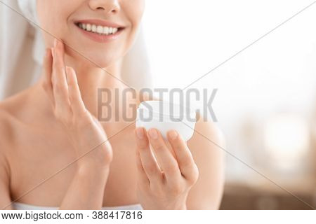 Face Care Concept. Cropped Of Unrecognizable Smiling Woman Wrapped In Towel Using Cream. Jar With Fa