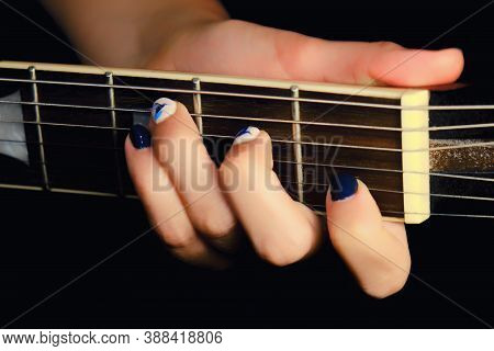 Female Hand With Manicure Lying On The Wooden Neck Of The Guitar. Woman Guitarist Clamped A Chord On
