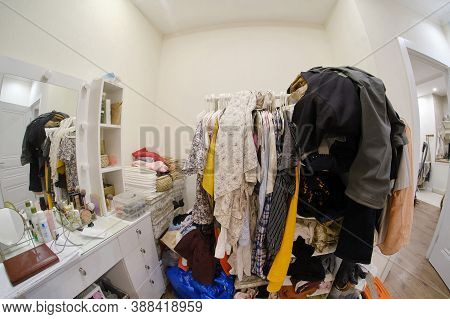 A Room Cluttered With Clothes And A Female Dressing Table With Cosmetics, No Closet, Background