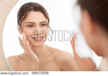 Closeup Of Cheerful Young Lady Using Face Cream At Home, Looking At Mirror And Smiling. Attractive W