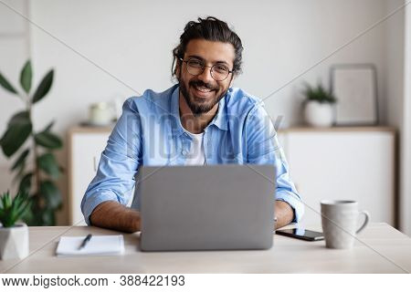 Successful Freelancer. Happy Millennial Indian Man Sitting At Desk With Laptop, Smiling And Posing A