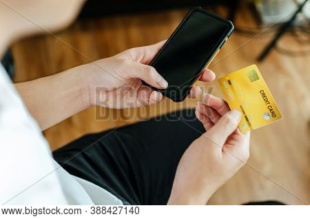 Man Holding Entering Code On Mobile Phone And Paying Bill With Credit Card On Desk At Home Office, D