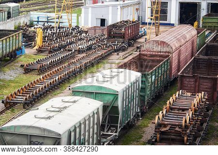 Freight Trains And Wheel Sets For Repair In A Railway Depot. Trains Stand In The Old Depot