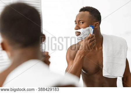 African American Man Shaving Face Covered With Shave Foam Standing Shirtless Near Mirror In Modern B