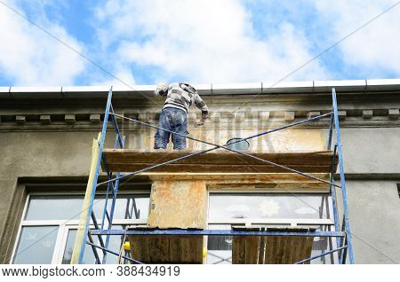 A Building Contractor On Scaffoldings Is Plastering, Applying Stucco And Renovating Painting The Fac