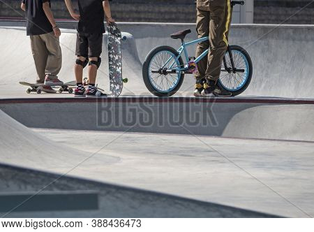 Young Active Teenagers With Skateboards And Bmx Bike In Concrete Skatepark