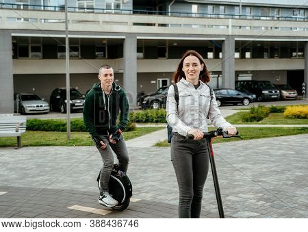 Young Man Riding Unicycle And Young Woman In Casual Wear Riding On Electric Kick Scooter On City Str