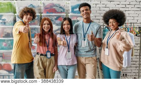 Young And Diverse Volunteer Group Smiling At Camera, Showing Thumbs Up While Posing In Front Of Boxe