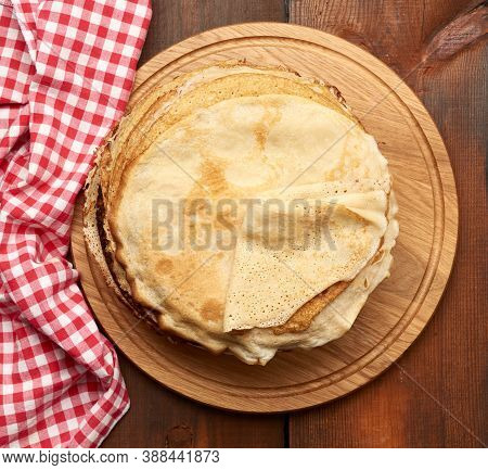Fried Round Pancakes On A Wooden Board, Brown Table, Top View