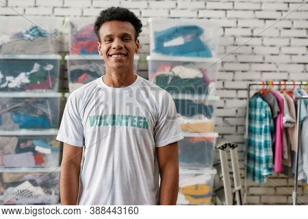 Cheerful Guy Smiling At Camera, Posing In Front Of Rack And Boxes Full Of Clothes, Young Male Volunt