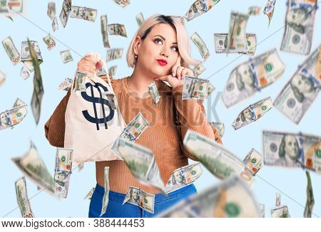 Young blonde plus size woman holding money bag with dollar symbol serious face thinking about question with hand on chin, thoughtful about confusing idea