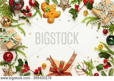 Christmas background with gingerbread cookies, gift boxes and branches of holly with red berries on white. Winter festive nature concept. Flat lay, copy space.
