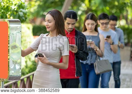 Asian woman using kiosk of food ordering with social distance queue in line befor getting in fast food restaurant. Online technology self service new normal restaurant concept.