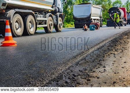 Close Up Of A New Road And Paving Machine On It That Was Recently Paved With Builders In Uniform On