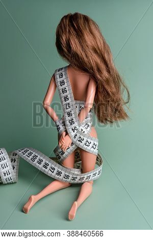 Doll Wrapped In Measuring Tape. Tied Up Fashion Doll, Weight Loss Concept. Fasting, Weightloss And S