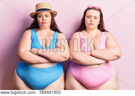 Young plus size twins wearing bikini skeptic and nervous, disapproving expression on face with crossed arms. negative person.