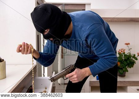 Male robber stealing valuable things from the house