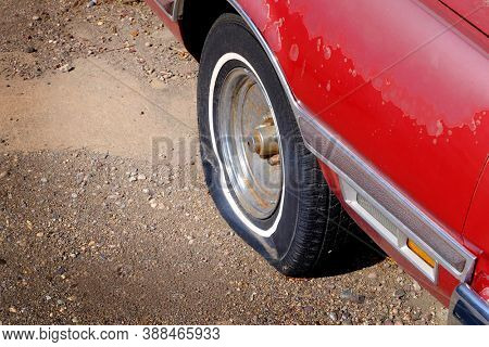 Flat tire red car vehicle deflated rubber wheel