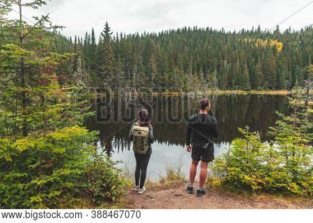 Canada travel destination outdoor activity couple tourists hiking to lake surrounded with pine trees forest. Autumn fall landscape nature.
