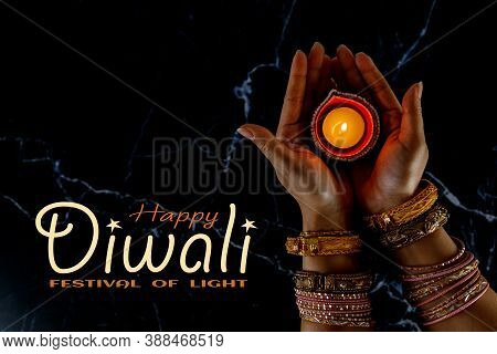 Happy Diwali - Woman Hands With Henna Holding Lit Candle Isolated On Dark Background. Clay Diya Lamp