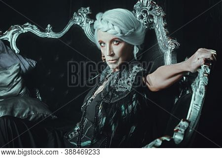 A beautiful old woman, a noble widow with gray hair and a rich black dress, sits on a vintage sofa in her old castle. Black widow. Fantasy world. Halloween.