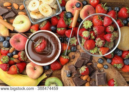 Fondue Fork With Strawberry In Bowl Of Melted Chocolate Surrounded By Other Fruits On Wooden Table,