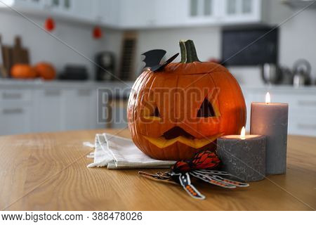 Pumpkin Jack O'lantern, Candles And Halloween Decor On Wooden Table In Kitchen, Space For Text