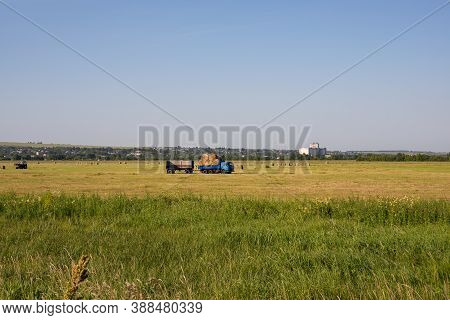 Nizhny Novgorod Region, Russia - July 8, 2020: Blue Kamaz Truck With A Trailer Carrying Rolls Of Hay