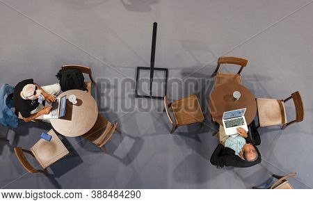 Trieste, Italy - September, 06: Top View Of Two Men Sitting At Table Working With His Notebook In Th