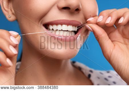 Young Woman Flossing Her Teeth On Blue Background, Closeup. Cosmetic Dentistry