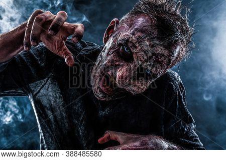 Scary Zombie On Dark Background. Halloween Monster