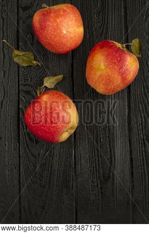 Top View Of Red Apples On The Black Woooden Background. Copy Space. Location Vertical.