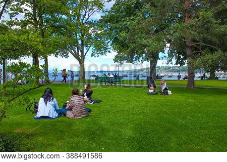 Geneva, Switzerland - June 17, 2016: The People Sitting On The Grass In A Park On The Waterfront Of