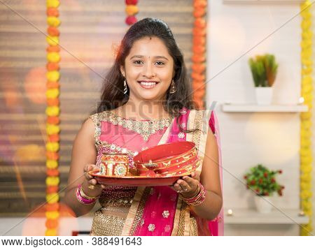 Portrit Shot Of Indian Married Woman In Traditional Dress Holding Karva Chauth Thali Or Plate During