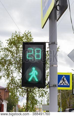 Pedestrian Traffic Light With Green Permissive Signal, Crosswalk Sign, Against Blurry Cloudy Sky Bac