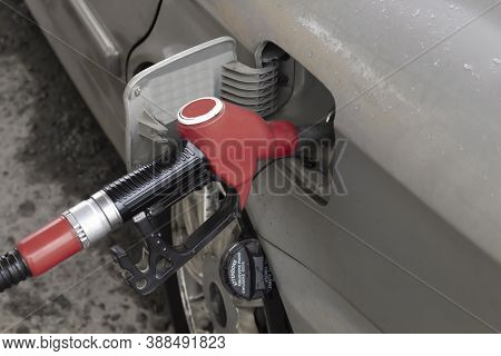 The Fuel Pistol Is Installed In The Vehicle Tank, Red Fuel Gun. Car Refueling And Fuel Prices Concep