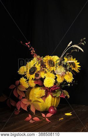 Flower Arrangement With Sunflowers In A Pumpkin On A Black Background. Thanksgiving And Copy Space C