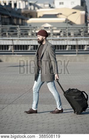 Adjust Living In New City. Man Bearded Hipster Travel With Luggage Bag On Wheels. Traveler With Suit