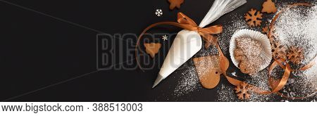 Christmas banner with gingerbread cookies, snowflakes and pastry bag with icing on black background with space for text, view from above. Homemade baking, Christmas and New Year traditions.