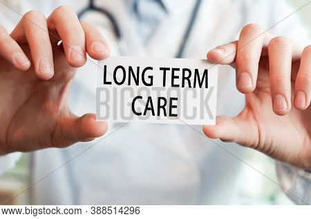 Doctor Holding A Card With Text Long Term Care