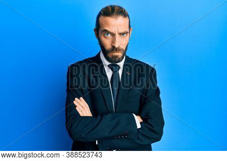 Attractive man with long hair and beard wearing business suit and tie skeptic and nervous, disapproving expression on face with crossed arms. negative person.