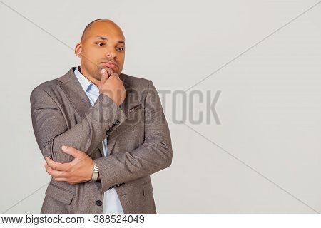 Handsome Young Male African American, Businessman In Jacket Looking To The Side And Thinking Touchin