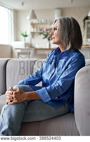 Classy Relaxed Mature Old Woman Relaxing Sitting On Couch At Home. Peaceful Middle Aged Grey-haired
