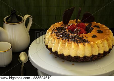 A Chocolate Cake And Flan (chocoflan) On A White Cake Plate And A Dark Background. Horizontal Shot A