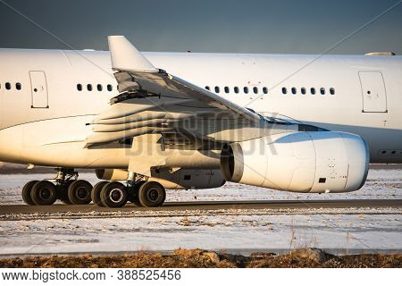 Closeup Of Landing Gear, Engine, Wing, Winglet And Fuselage Of Passenger Aircraft Taxing On Runway,