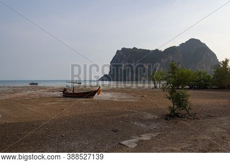 Railay East Beach At Low Tide, In The Background Of The Mountain, On The Beach Boat Stranded